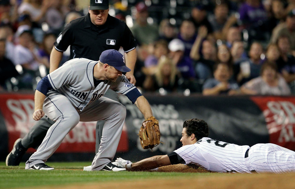 . San Diego Padres third baseman Chase Headley reaches for Colorado Rockies\' Nolan Arenado as Arenado slides safely into third base on a triple in the fifth inning of a baseball game in Denver on Tuesday, Aug. 13, 2013.(AP Photo/Joe Mahoney)