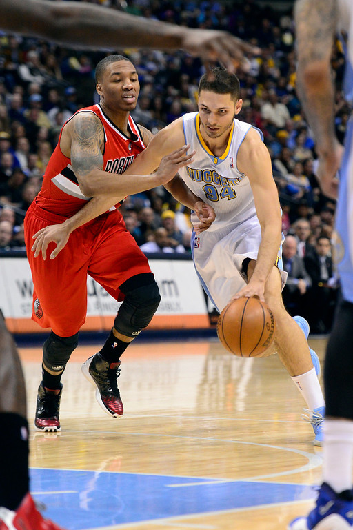 . DENVER, CO - APRIL 14: Evan Fournier (94) of the Denver Nuggets drives on Damian Lillard (0) of the Portland Trail Blazers during the first half of action. The Denver Nuggets play the Portland Trail Blazers at the Pepsi Center. (Photo by AAron Ontiveroz/The Denver Post)