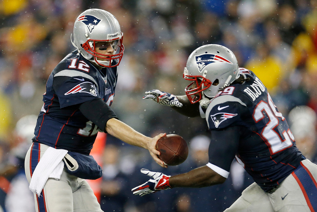 . New England Patriots quarterback Tom Brady (12) hands off the ball to running back LeGarrette Blount (29) during the first half of an AFC divisional NFL playoff football game against the Indianapolis Colts in Foxborough, Mass., Saturday, Jan. 11, 2014. (AP Photo/Michael Dwyer)