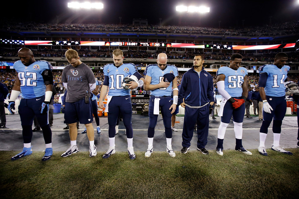 . Tennessee Titans players including linebacker Will Witherspoon (92), quarterback Jake Locker (10), quarterback Matt Hasselbeck (8), linebacker Akeem Ayers (56) and wide receiver Michael Preston (14) bow their heads during a moment of silence for the victims of the Sandy Hook Elementary School shootings in Newtown, Conn., before an NFL football game against the New York Jets, Monday, Dec. 17, 2012, in Nashville, Tenn. (AP Photo/Mark Humphrey)