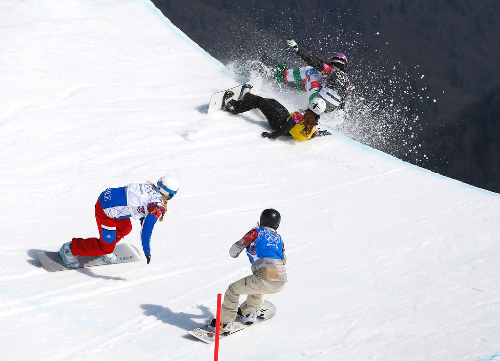 . Italy\'s Michela Moioli, top right, and Bulgaria\'s Alexandra Jekova crash off a drop, as France\'s Chloe Trespeuch, left, and Faye Gulini of the United States follow during the women\'s snowboard cross final at the Rosa Khutor Extreme Park, at the 2014 Winter Olympics, Sunday, Feb. 16, 2014, in Krasnaya Polyana, Russia. (AP Photo/Sergei Grits)