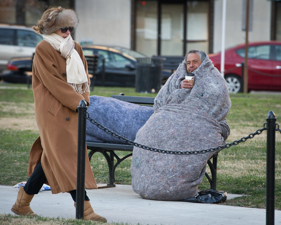 . A woman bundled against the cold walks past a homeless man in McPherson Square as temperatures dipped into the single digits Fahrenheit and minus degrees with the wind chill on January 7, 2014 in Washington, DC. A blast of bone-chilling cold reaching lows not seen in two decades gripped the United States early Tuesday, snarling air travel, closing schools and prompting calls for people to stay inside. Superlatives of cold-talk abounded, even in midwestern states used to chest-high snow and bitter cold, as the National Weather Service said the deep freeze was making its way east. AFP PHOTO/MLADEN ANTONOV/AFP/Getty Images