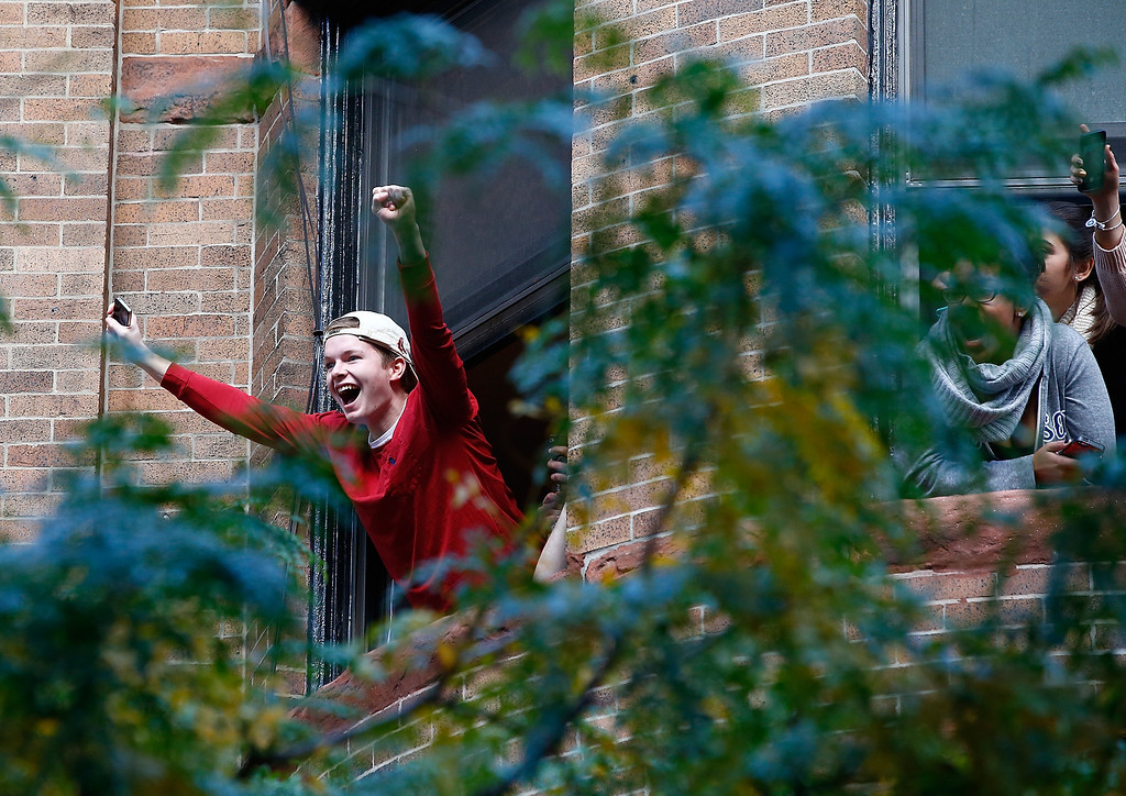 . BOSTON, MA - NOVEMBER 02:  Boston Red Sox fans cheer from a window during the World Series victory parade on November 2, 2013 in Boston, Massachusetts.  (Photo by Jared Wickerham/Getty Images)