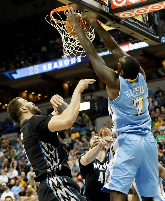 . Minnesota Timberwolves\' Nikola Pekovic, left, of Montenegro, looks on as Denver Nuggets\' J.J. Hickson dunks in the second half of an NBA basketball game on Wednesday, Nov. 27, 2013, in Minneapolis. The Nuggets won 117-110. (AP Photo/Jim Mone)