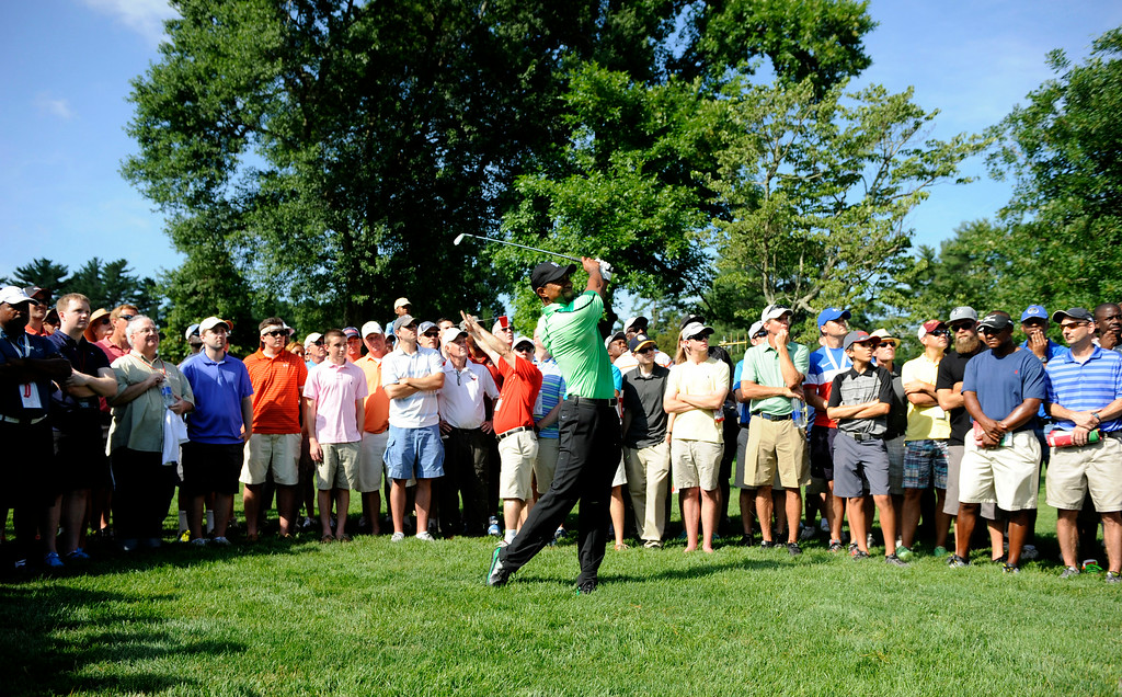. Tiger Woods watches his shot from the rough on the 15th hole during the first round of the Quicken Loans National golf tournament, Thursday, June 26, 2014, in Bethesda, Md. (AP Photo/Nick Wass)