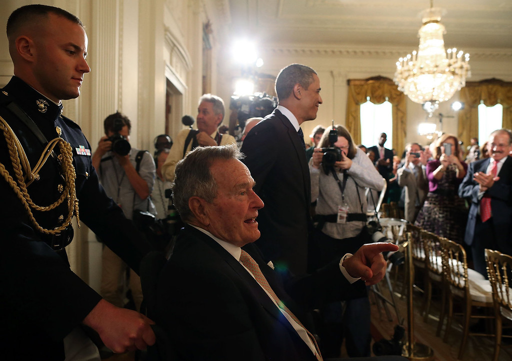 . Former U.S. President George H. W. Bush sits in a wheelchair as U.S. President Barack Obama (R) escorts him into the East Room during an event at the White House, July 15, 2013 in Washington, DC. Bush joined President Obama in hosting the event to honor the 5,000th Daily Point of Light Award winner.  (Photo by Mark Wilson/Getty Images)