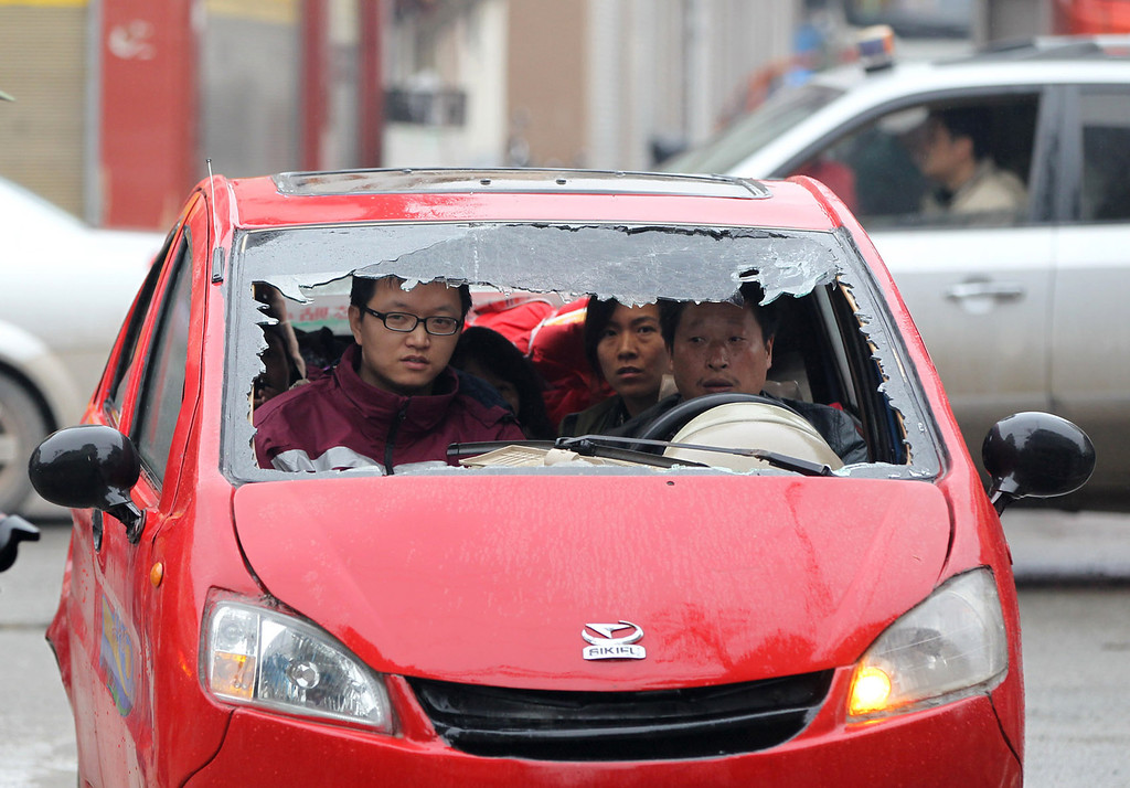 . This photo taken on April 23, 2013 shows people inside a damaged car in Lingguan township of Baoxing county in Yaan, southwest China\'s Sichuan province. Tens of thousands of homeless survivors of China\'s devastating quake are living in makeshift tents or on the streets, facing shortages of food and supplies as well as an uncertain future.  AFP PHOTOSTR/AFP/Getty Images