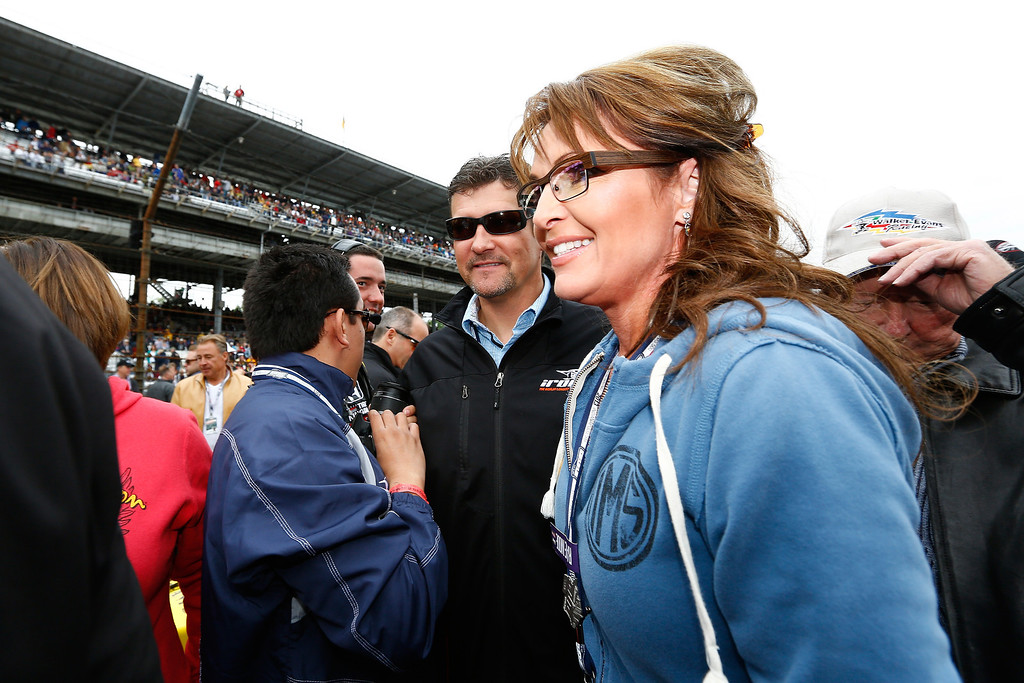 . Former vice presidential candidate Sarah Palin (R) and her husband, Todd, walk through pit road during the IZOD IndyCar Series 97th running of the Indianpolis 500 mile race at the Indianapolis Motor Speedway on May 26, 2013 in Indianapolis, Indiana.  (Photo by Michael Hickey/Getty Images)