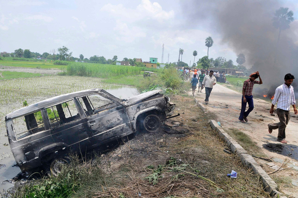 . People walk past a vehicle that was burnt by protesters as they campaign against contaminated meals that were given to children on Tuesday, at Chapra in the eastern Indian state of Bihar July 17, 2013. At least 20 children died and dozens were taken to hospital with apparent food poisoning after eating a meal provided for free at their school in the district of Chapra in the eastern Indian state of Bihar, the education minister said on Wednesday, sparking violent protests. REUTERS/Stringer
