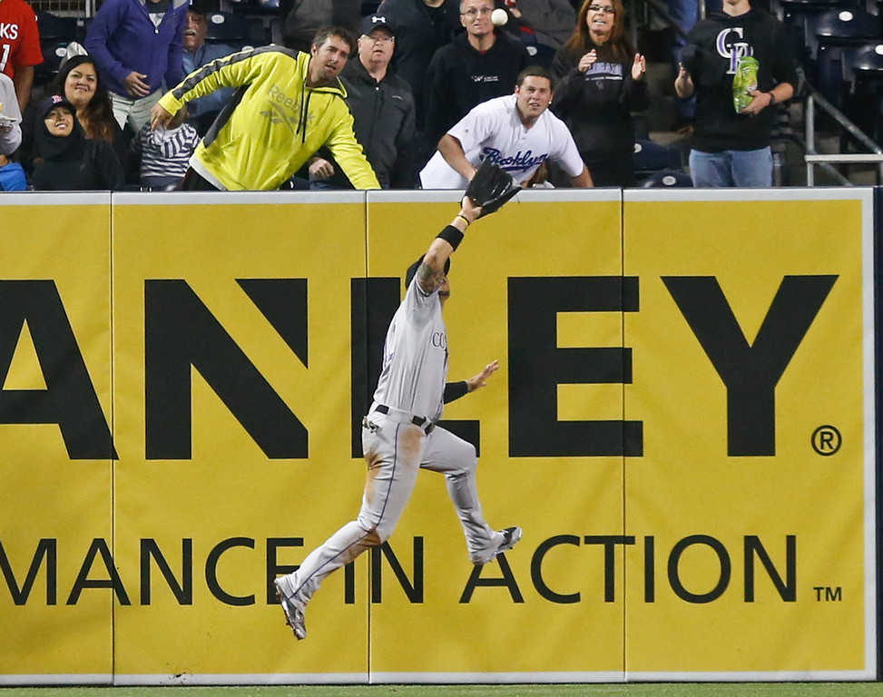 . Colorado Rockies left fielder Carlos Gonzalez goes up to snare a deep drive hit by San Diego Padres\' Nick Hundley with a runner on base in the seventh inning of a baseball game Tuesday, April 15, 2014, in San Diego. (AP Photo/Lenny Ignelzi)