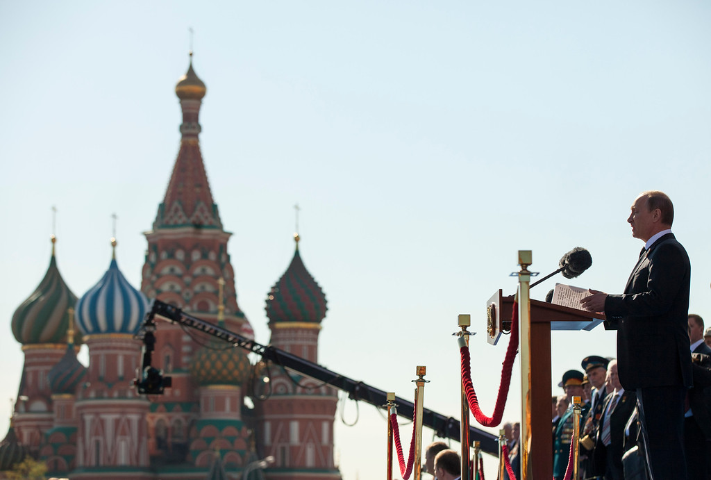 . Russian President Vladimir Putin, right, addresses troops and WWII veterans before the Victory Day Parade, which commemorates the 1945 defeat of Nazi Germany in Moscow,  Russia, Thursday, May 9, 2013, with the St. Basel Cathedral in the background. Russian President Vladimir Putin has said at the annual military parade on Red Square that Russia will be a guarantor of world security. Putin\'s short speech Thursday came at the culmination of Victory Day, marking the defeat of Nazi Germany 68 years ago. It is Russia\'s most important secular holiday, honouring the huge military and civilian losses of World War II and showing off the country\'s modern arsenal. (AP Photo/Alexander Zemlianichenko)