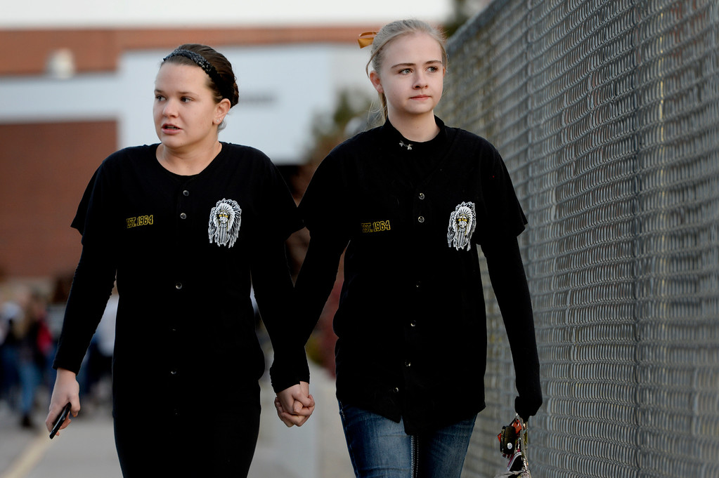 ". Seniors Amanda Bridges, right, and Melissa Tombaugh make their way to the tribute area before visiting Arapahoe High School in Centennial, CO December 19, 2013. Seniors and Juniors returned to the school for two hour periods Thursday, Sophomores and Freshmen will return on Friday. Melissa said, ""it\'s rough, I\'m a little nervous.\"" The victim from Friday�s shooting at Arapahoe High School, Claire Davis, 17, remains in critical condition. She was shot on Friday when classmate Karl Pierson opened fire in the school. The gunman died from a self-inflicted gunshot wound. (Photo By Craig F. Walker / The Denver Post)"