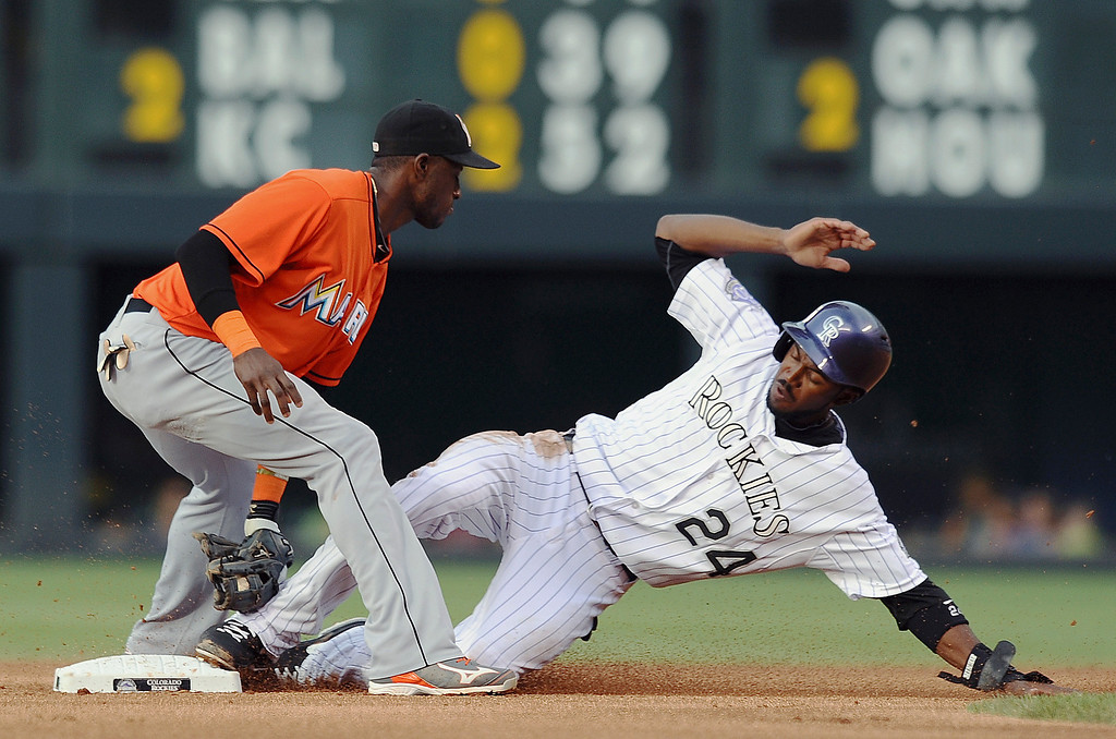 . Miami Marlins shortstop Adeiny Hechavarria tags out Colorado Rockies Dexter Fowler at second base on a steal attempt in the first inning of a baseball game Tuesday, July 23, 2013, in Denver. (AP Photo/Chris Schneider)