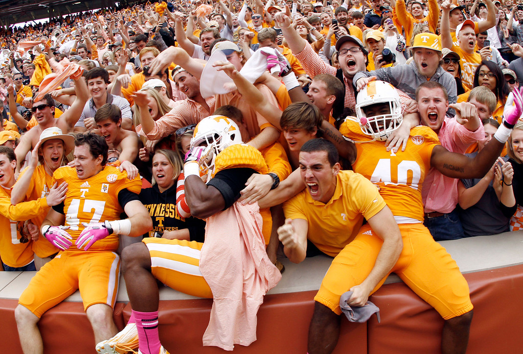 . Tennessee linebacker Raiques Crump (40), defensive back Michael F. Williams, center, and linebacker John Propst (47) celebrate with fans after their 23-21 victory over South Carolina in an NCAA college football game on Saturday, Oct. 19, 2013 in Knoxville, Tenn. (AP Photo/Wade Payne)