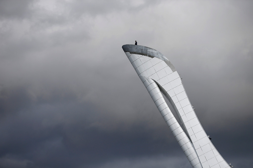 . A worker is dwarfed against the sky as he stands at the top of the Olympic cauldron ahead of the 2014 Winter Olympics, Tuesday, Feb. 4, 2014, in Sochi, Russia. (AP Photo/Wong Maye-E)
