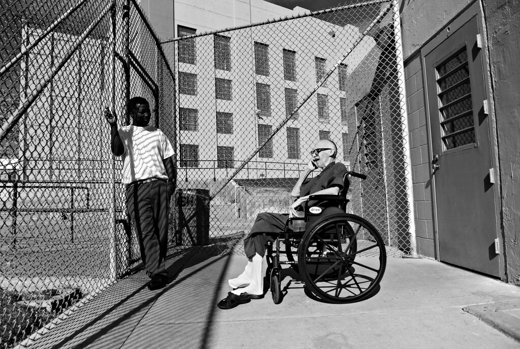 . CANYON CITY, CO. - NOVEMBER 08: While having a good day, Robert Bryan, right, decides he feels well enough to go out to the prison yard for the first time in two months, November 08, 2012.  He rarely left his infirmary bed due to his battle with liver cancer. Bryan kicked off his sandals in the sunlight while he spoke to his friend, caretaker and fellow inmate Wayne Rose. (Photo By RJ Sangosti/The Denver Post)