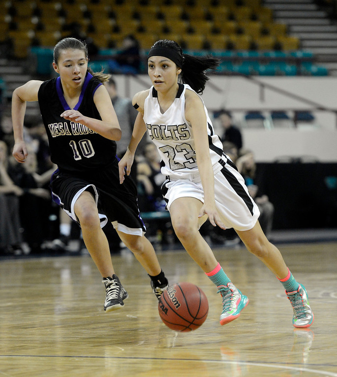 . DENVER, CO. - MARCH 9TH: Jaylyn Duran, Pueblo South, right, drives up court against the defense of, Kaylee Gatzke, left, Mesa Ridge, in the second half of the 4A �Great Eight� game at the Denver Coliseum, Saturday morning, March 9th, 2013. Pueblo South won 54-33 to advance to the Final Four at the CU Events Center, March 14th, 2013. (Photo By Andy Cross The Denver Post)