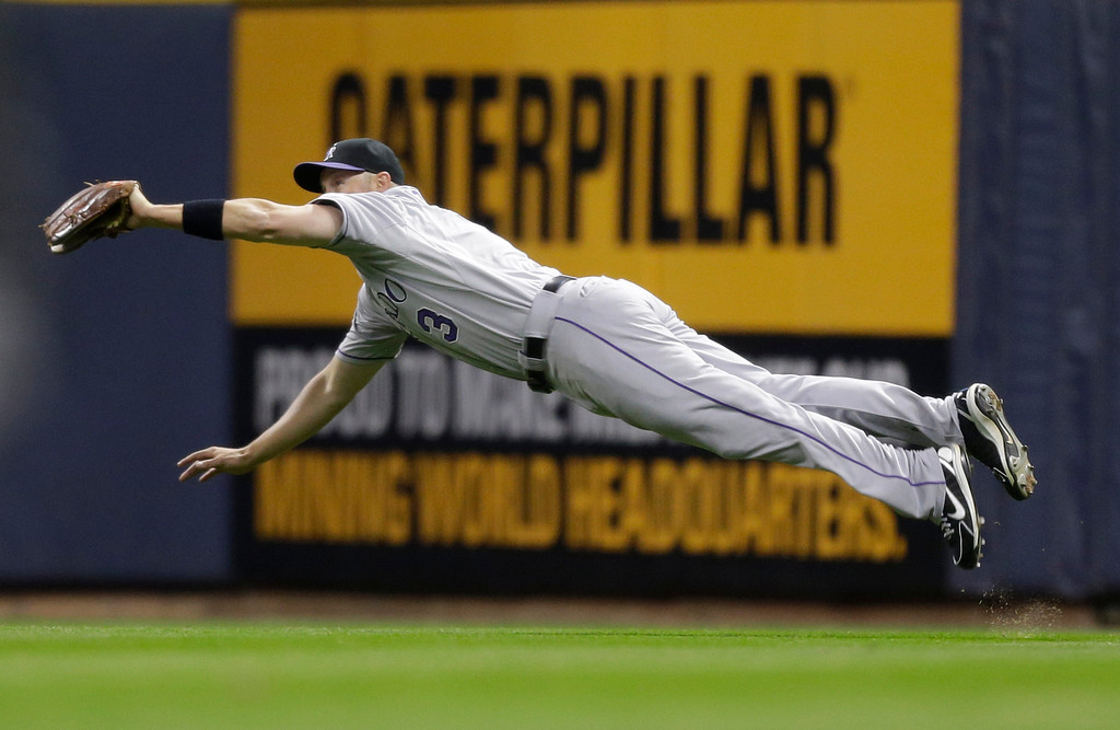 . Colorado Rockies\' Michael Cuddyer makes a diving catch on a line drive hi by Milwaukee Brewers\' Alex Gonzalez during the eighth inning of a baseball game Tuesday, April 2, 2013, in Milwaukee. (AP Photo/Jeffrey Phelps)