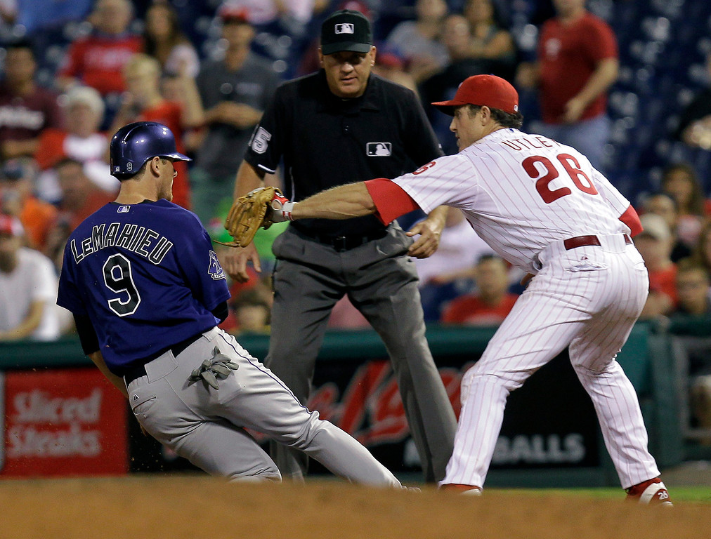 . Colorado Rockies\' DJ LeMahieu is tagged out at first on a pick off by Philadelphia Phillies\' Chase Utley in the ninth inning of a baseball game, Monday, Aug. 19, 2013, in Philadelphia. Phillies defeated the Rockies 5-4. (AP Photo/Laurence Kesterson)