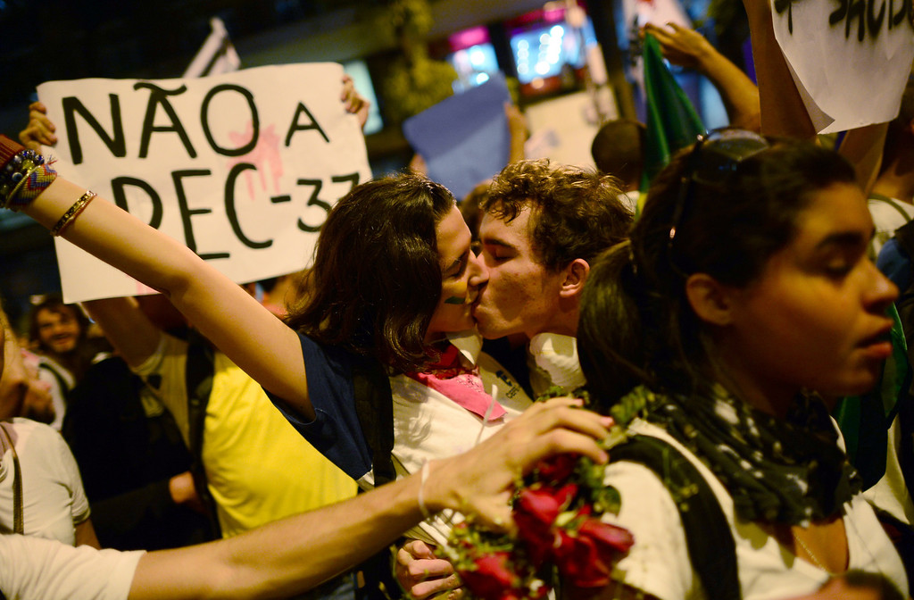 . A couple kiss as demonstrators march in Rio de Janeiro downtown on June 17, 2013, against higher public transportation fares and the use of public funds to disrupt international football tournaments. CHRISTOPHE SIMON/AFP/Getty Images