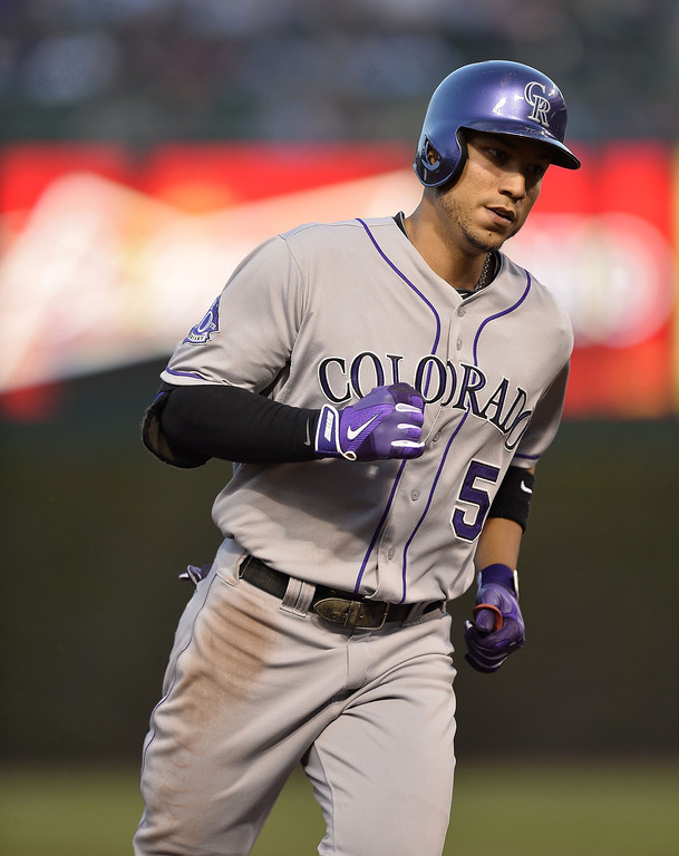 . Carlos Gonzalez #5 of the Colorado Rockies rounds the bases after hitting a solo home run during the third inning against the Chicago Cubs on May 14, 2013 at Wrigley Field in Chicago, Illinois.    (Photo by Brian Kersey/Getty Images)