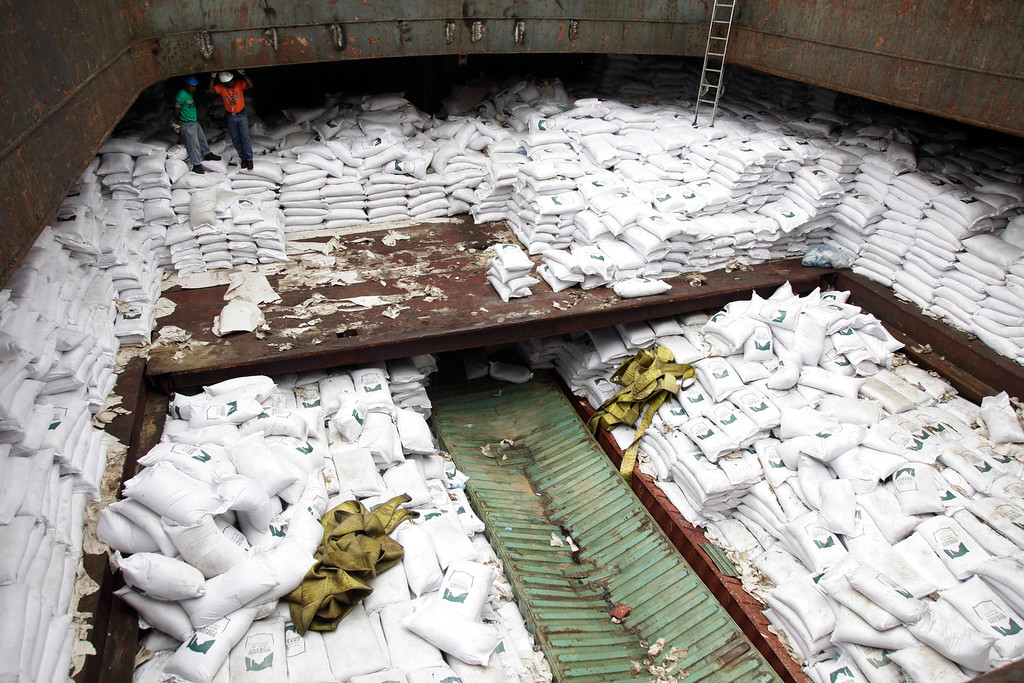 . Panamanian workers stand atop sacks of sugar inside a container of a North Korean-flagged ship at the Manzanillo International container terminal on the coast of Colon City, Panama, Tuesday, July 16, 2013.  (AP Photo/Arnulfo Franco)