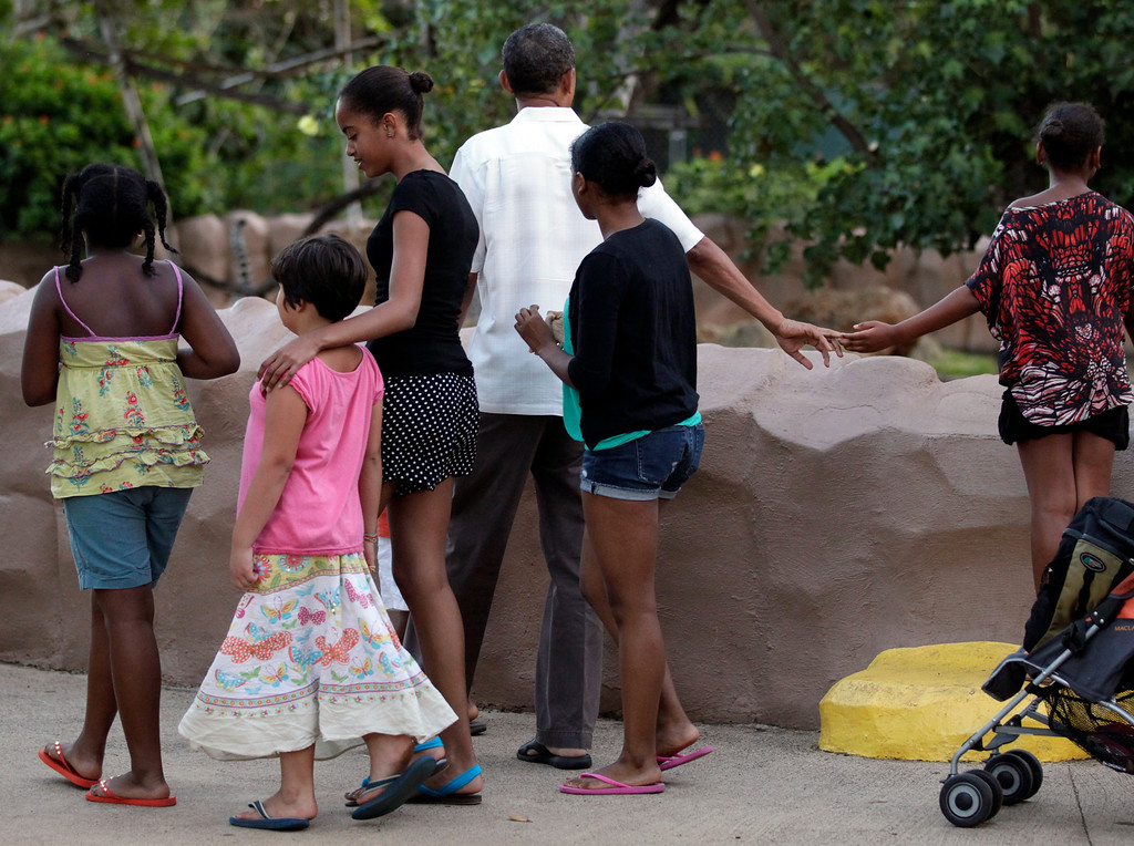 . Hands touching, President Barack Obama and his daughter Sasha Obama, far right, walk with other family friends through Honolulu Zoo in Honolulu, Monday, Jan. 3, 2011. (AP Photo/Carolyn Kaster)