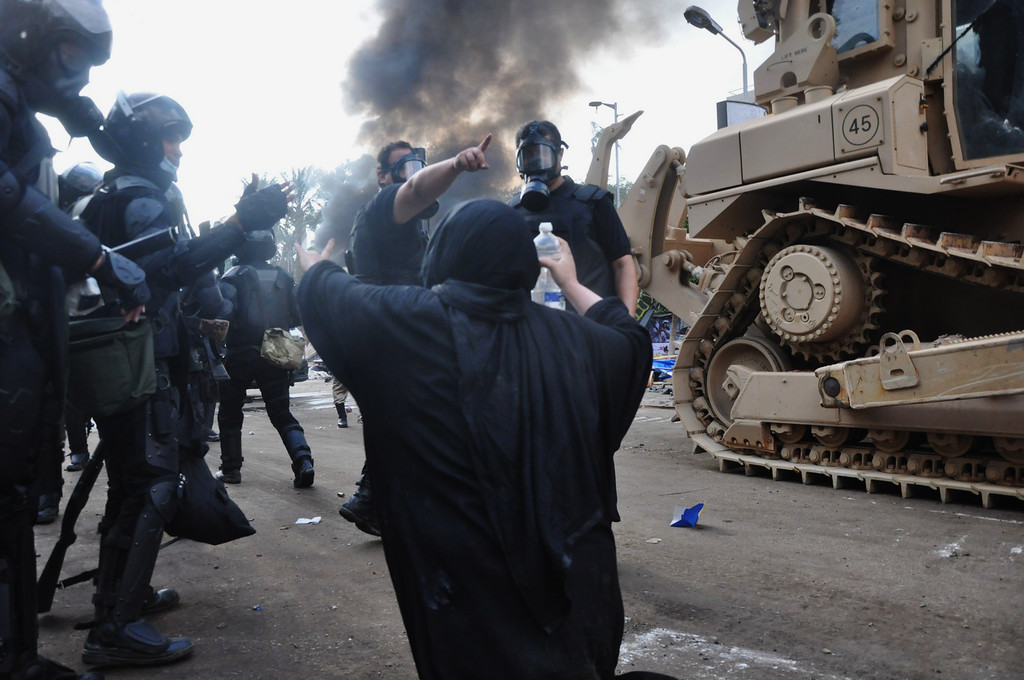 . A supporter of ousted Islamist President Mohammed Morsi approaches Egyptian security forces as they clear a sit-in camp set up  near Cairo University in Cairo\'s Giza district, Egypt, Wednesday, Aug. 14, 2013.  (AP Photo/Hussein Tallal)