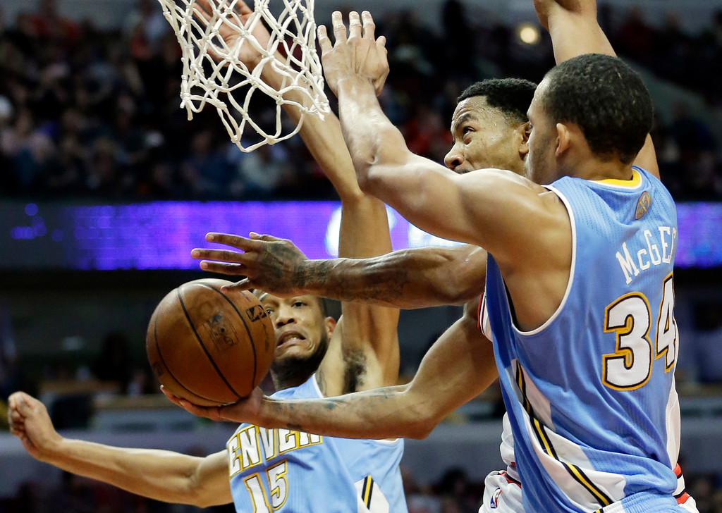 . Chicago Bulls guard Derrick Rose, center, drives to the basket between Denver Nuggets forward Anthony Randolph, left, and center JaVale McGee during the second half of an NBA preseason basketball game in Chicago on Friday, Oct. 25, 2013. The Bulls won 94-89. (AP Photo/Nam Y. Huh)