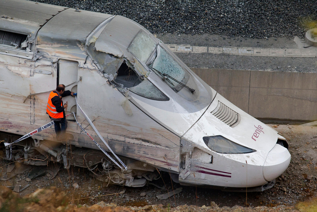 . A rail personnel works next to the cabin of a derailed train following an accident in Santiago de Compostela, Spain, on Thursday, July 25, 2013. (AP Photo/Lalo Villar)