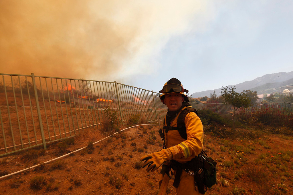 . A firefighter works to protect homes from a fast-moving brush fire in the Newbury Park area of Ventura County May 2, 2013.  REUTER/Patrick T. Fallon