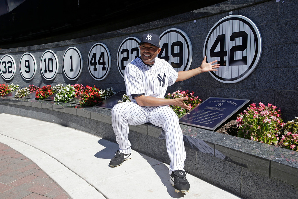 . New York Yankees relief pitcher Mariano Rivera (42) poses with a plaque showing his retired number in Monument Park during a pregame ceremony at Yankees Stadium before abaseball game against the San Francisco Giants, Sunday, Sept. 22, 2013, in New York. The 13-time All-Star closer is retiring at the end of this season.  (AP Photo/Kathy Willens, Pool)