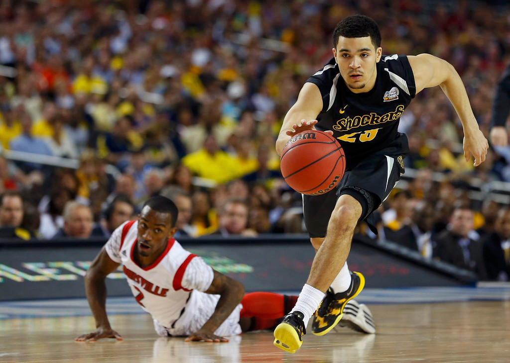. Wichita State Shockers guard Fred VanVleet (R) dribbles past Louisville Cardinals guard Russ Smith during the first half of their NCAA men\'s Final Four basketball game in Atlanta, Georgia April 6, 2013. REUTERS/Chris Keane