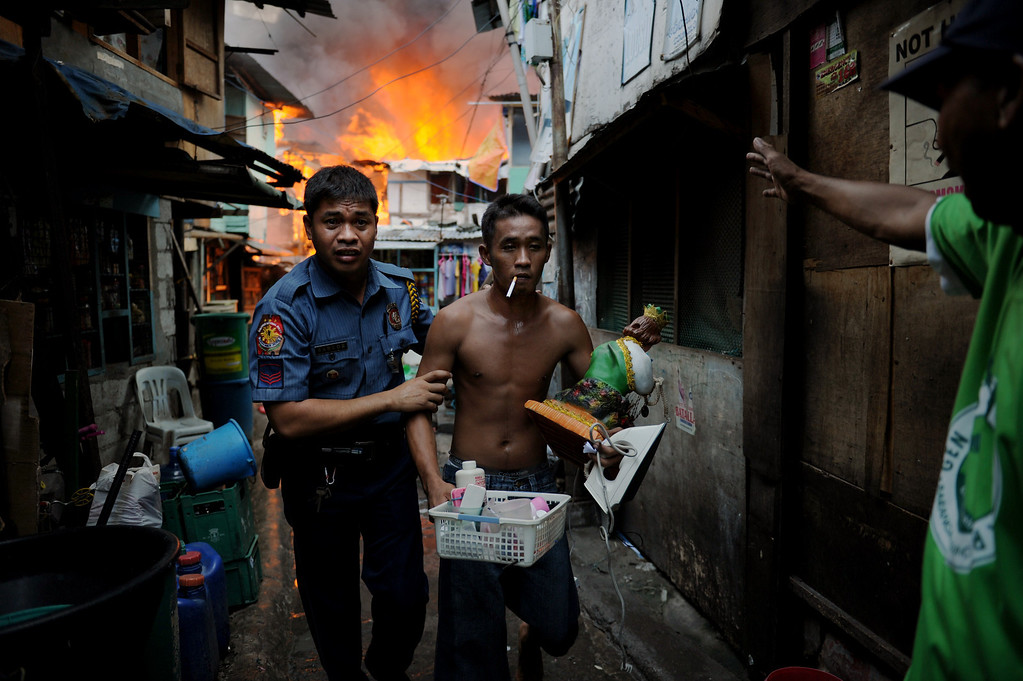 . A policeman (L) leads out a resident carrying salvaged belongings from his burning house as a fire engulfs a shanty town in the financial district of Manila on July 11, 2013, leaving more than 1,000 people homeless according to city officials. There were no immediate reports of casualties from the blaze, which occurred mid-morning amid government plans to relocate thousands of families living in areas vulnerable to floods and typhoons. TED ALJIBE/AFP/Getty Images