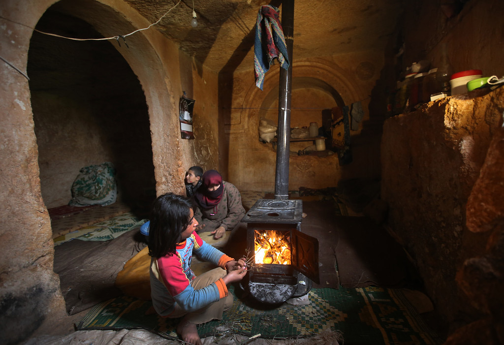 . Nihal, 9, puts olive tree branches inside a wooden stove at an underground Roman tomb which they use shelter from Syrian government forces shelling and airstrikes, at Jabal al-Zaweya, in Idlib province, Syria, Thursday Feb. 28, 2013. Across northern Syria, rebels, soldiers, and civilians are making use of the country\'s wealth of ancient and medieval antiquities to protect themselves from Syria\'s two-year-old war. They are built of thick stone that has already withstood centuries, and are often located in strategic locations overlooking towns and roads. (AP Photo/Hussein Malla)