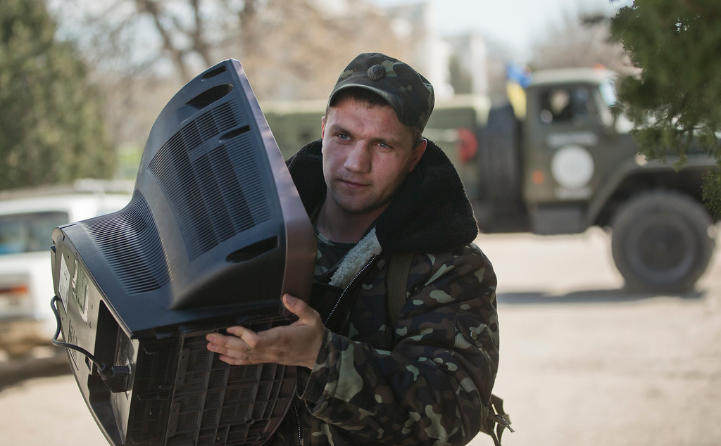 . An Ukrainian airman carries a TV set as he leaves the Belbek air base, outside Sevastopol, Crimea, Friday, March 21, 2014. The base commander Col. Yuliy Mamchur said he was asked by the Russian military to turn over the base but is unwilling to do so until he receives orders from the Ukrainian defense ministry. (AP Photo/Vadim Ghirda)