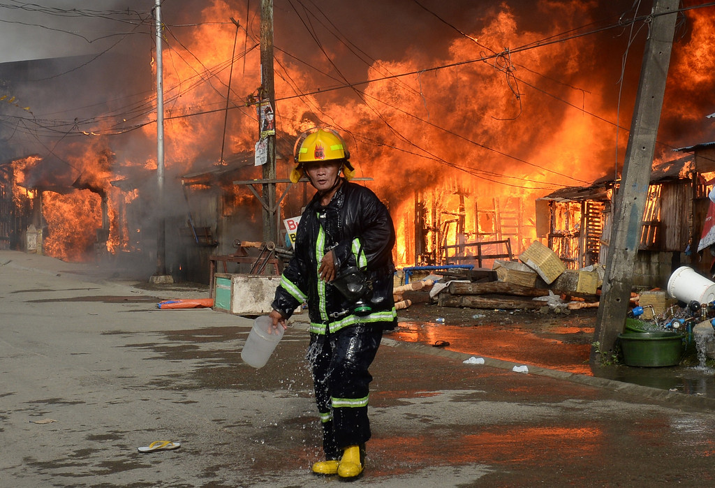 . A fireman walks past burning houses during a fire fight between government forces and Muslim rebels as stand-off entered its fourth day in Zamboanga City on the southern island of Mindanao on September 12, 2013. AFP PHOTO/TED ALJIBE/AFP/Getty Images