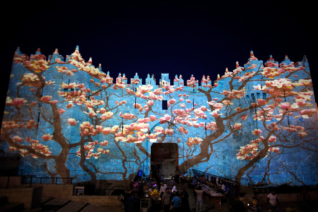". People stand near Damascus gate outside Jerusalem\'s Old City as it is projected with images during the ""Jerusalem Light 2013\"" Festival June 5, 2013. The festival opened on Wednesday night and will run for a week in the Old City of Jerusalem, hosting Israeli and international artists who will display their installations throughout the week. REUTERS/Ammar Awad"