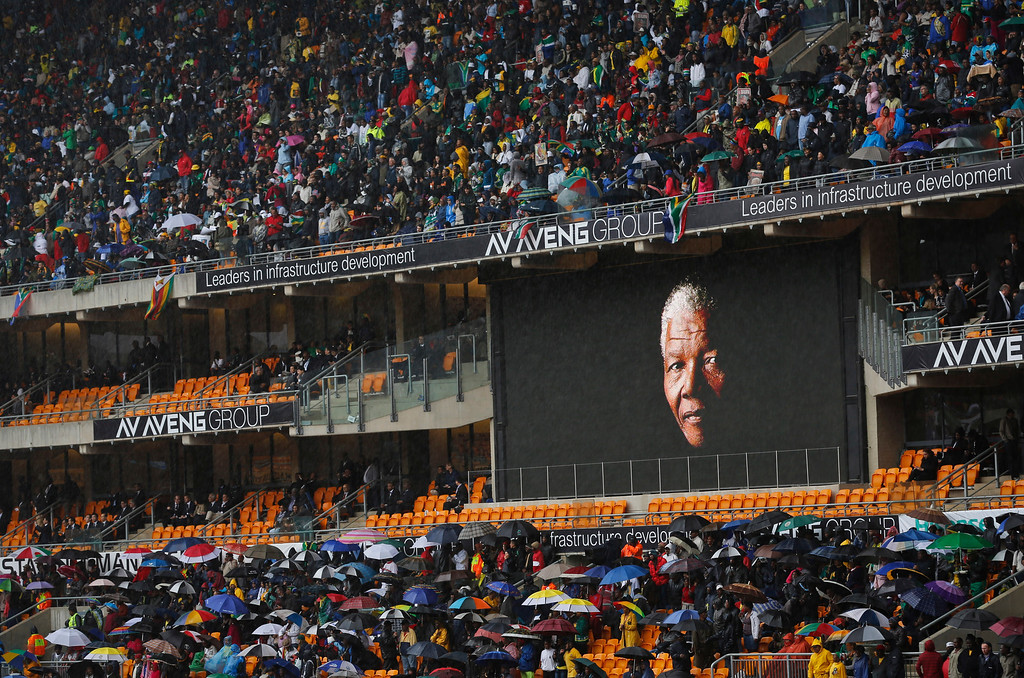 . The face of Nelson Mandela is shown on a large billboard in the stands at the memorial service for former South African President Nelson Mandela at the FNB stadium in Johannesburg, South Africa Tuesday, Dec. 10, 2013. (AP Photo/Ben Curtis)
