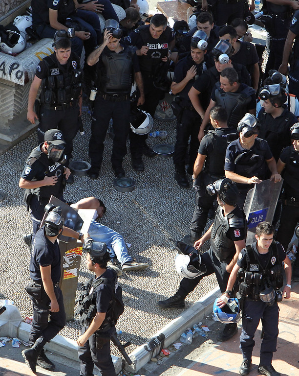 . A protester lays on the ground after being detained by police during clashes at the Taksim Square in Istanbul Tuesday, June 11, 2013.  (AP Photo/Thanassis Stavrakis)
