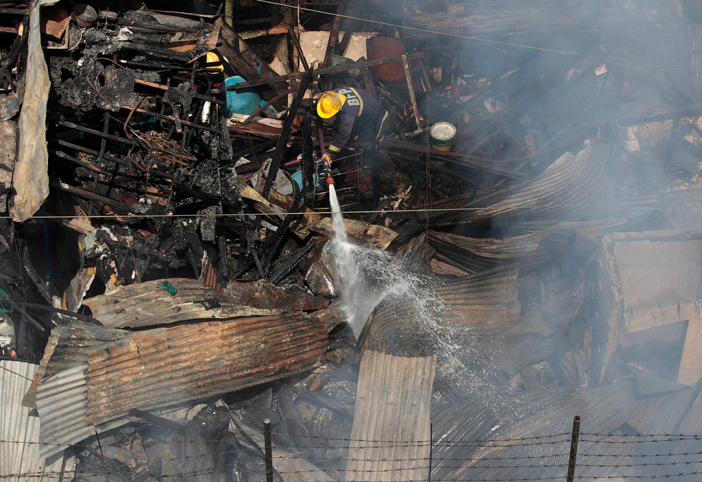 . A Filipino fireman aims his hose at the still smoldering remains of a house at the financial district of Makati, south of Manila, Philippines on Thursday, July 11, 2013. Investigators are still checking the cause of the fire which gutted a slum colony and left hundreds homeless. (AP Photo/Aaron Favila)