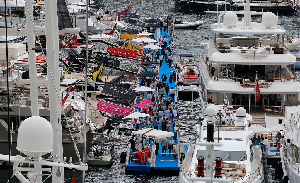 . Visitors walk between yachts at the 24th edition of the Monaco Yacht Show, Wednesday, Sept. 25, 2013, in Monaco.  (AP Photo/Lionel Cironneau)