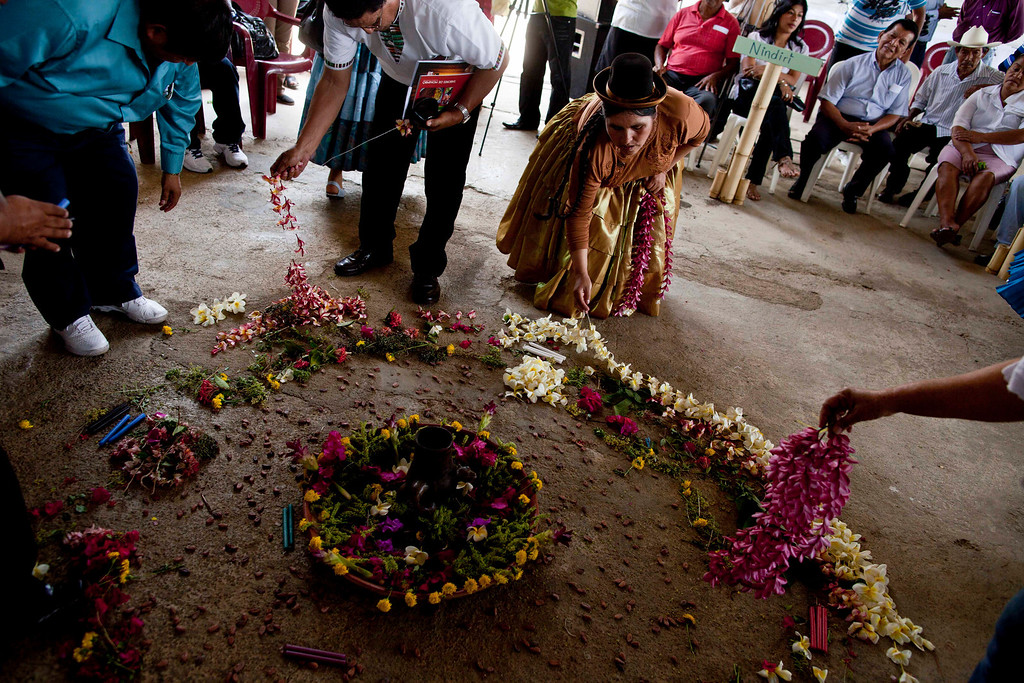 ". Peru\'s Congresswoman, Quechua Indian Claudia Coari, center, puts flowers on an altar named ""Offering to the earth\"" during visit the indigenous neighborhood of Monimbo in Masaya, Nicaragua, Wednesday, April 10, 2013.  Coari is in Nicaragua, along with legislators from Nicaragua, Peru, Bolivia, Chile, Colombia, Ecuador, Guatemala, Honduras, Mexico, Panama and Venezuela, for the 13th ordinary session of the Indigenous Parliament of America. (AP Photo/Esteban Felix)"