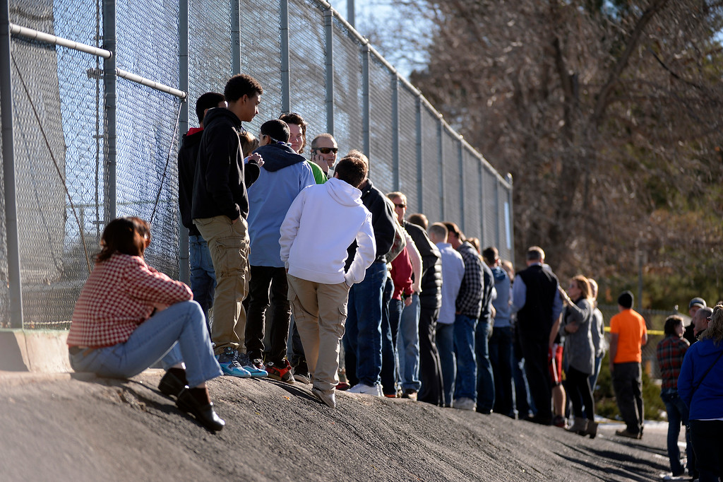 . CENTENNIAL, CO - Parents stand along the tennis court fence hoping to see if their child is standing out side on the football field after a gunman was spotted inside Arapahoe High School December 13, 2013. The gunman was targeting a teacher at the school. The gunman shot two students in the process and then turned the gun on himself. DECEMBER 13:  (John Leyba, The Denver Post)