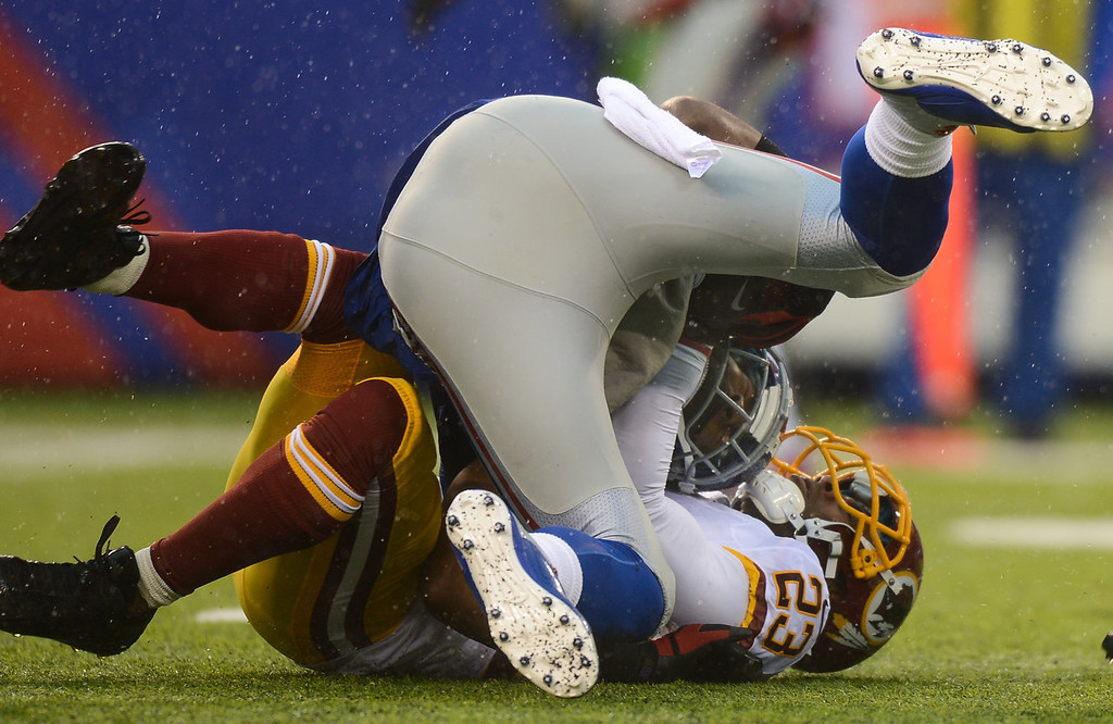 . Wide receiver Hakeem Nicks #88 of the New York Giants is tackled by cornerback DeAngelo Hall #23 of the Washington Redskins in the first half  at MetLife Stadium on December 29, 2013 in East Rutherford, New Jersey. (Photo by Ron Antonelli/Getty Images)
