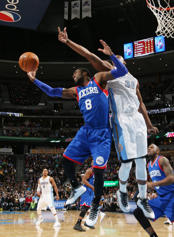 . Philadelphia 76ers guard Tony Wroten, left, pulls in a rebound in front of Denver Nuggets forward Darrell Arthur during the third quarter of the Sixers\' 114-102 victory in an NBA basketball game in Denver on Wednesday, Jan. 1, 2014. (AP Photo/David Zalubowski)