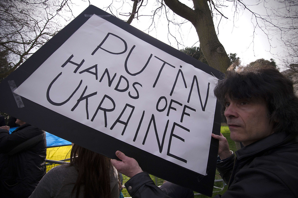 . An anti-Russian protester holds a placard during a demonstration outside the residence of the US ambassador to the UK in central London on March 14, 2014, where US Foreign Secretary John Kerry meets his Russian counterpart Sergei Lavrov. The United States and Russia failed to resolve a Cold-War-style crisis sparked by Moscow\'s military intervention in Crimea and the Ukrainian peninsula\'s weekend referendum on joining Kremlin rule. CARL COURT/AFP/Getty Images