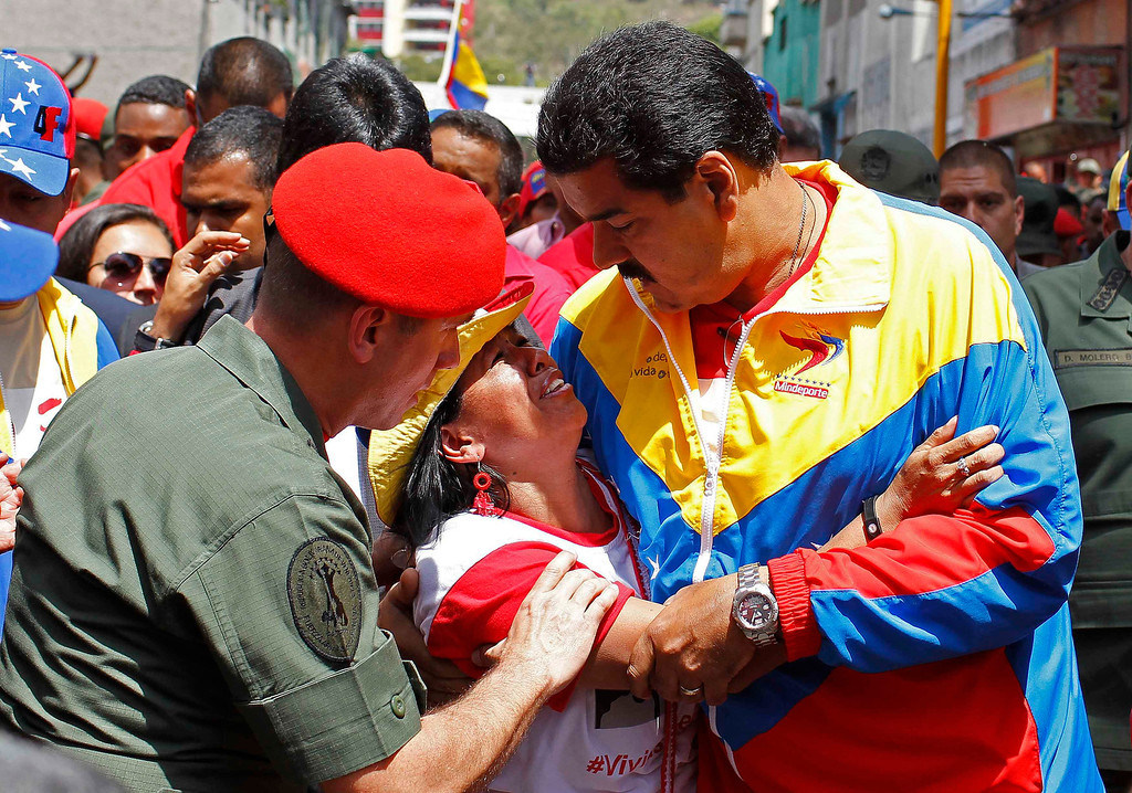 . Venezuela\'s Vice President Nicolas Maduro consoles a supporter of deceased Venezuelan leader Hugo Chavez, as his coffin is driven through the streets of Caracas, March 6, 2013. REUTERS/Carlos Garcia Rawlins