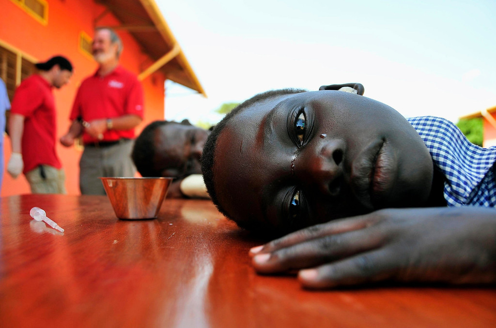 . A girl with hearing challenges cries after her ears were cleaned during an event held by Starkey Hearing Foundation at St. Monica in Gulu, 364 km (226 miles) north of Uganda\'s capital Kampala, March 13, 2012. REUTERS/Xavier Toya