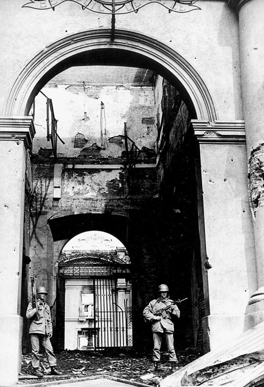 . In this Sept. 11, 1973 file photo, soldiers stand guard at the main entrance of La Moneda presidential palace after it was bombed during a military coup led by Gen. Augusto Pinochet that brought down the government of President Salvador Allende in Santiago, Chile. On Sept. 11, 2013, Chile marks the 40th anniversary of the coup.  (AP Photo/El Mercurio, File)